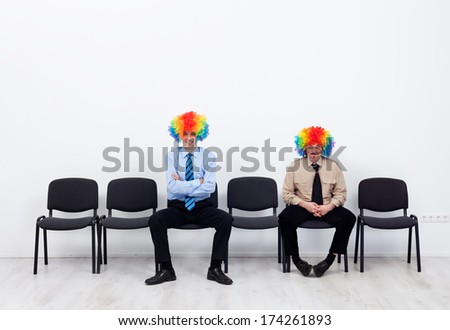 Businessmen wearing clown wigs waiting - sitting on row of chairs - stock photo