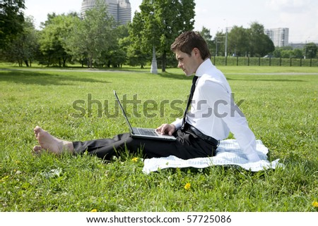 businessmen working at laptop on grass outdoor in park - stock photo
