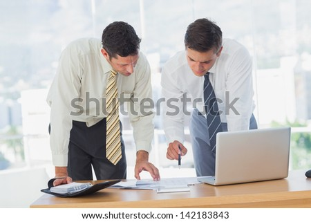 Businessmen working together leaning on desk in the office - stock photo