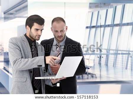 Businessmen working with laptop at office, discussing. Copyspace - stock photo