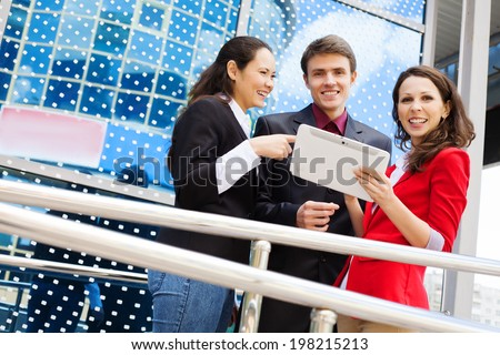 Businesspeole Working On Tablet Computer Outside Office - stock photo