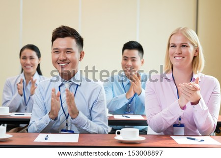 Businesspeople applauding at the meeting on the foreground - stock photo