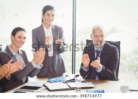 Businesspeople applauding in conference room during meeting - stock photo