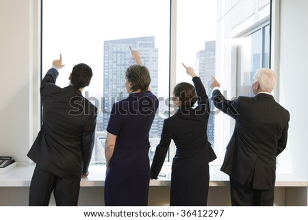 Businesspeople by window pointing up. - stock photo