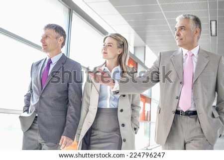Businesspeople communicating while walking on train platform - stock photo