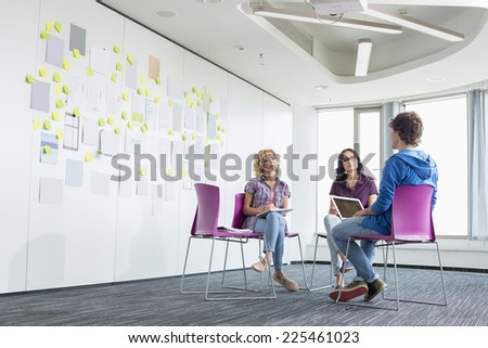 Businesspeople discussing in creative office space - stock photo