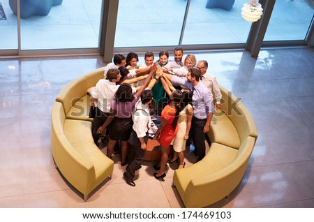 Businesspeople Giving Each Other High Five In Office Lobby - stock photo
