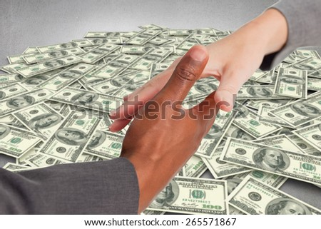 Businesspeople going to shake hands against pile of dollars - stock photo