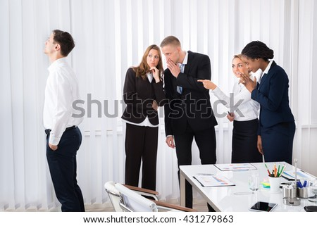 Businesspeople Gossiping Behind Young Colleague In Office - stock photo