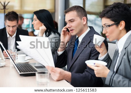 businesspeople having a business meeting using laptop computer in cafe - stock photo