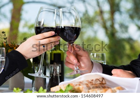 Businesspeople having business lunch in a fine dining restaurant - stock photo
