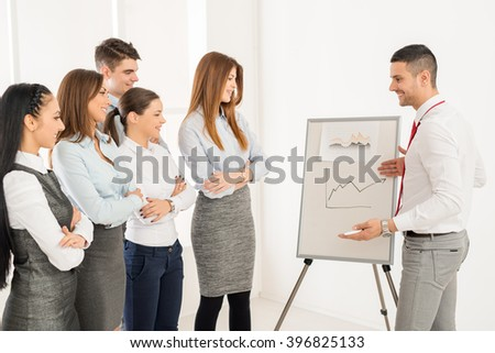 Businesspeople having meeting in a office. Young businessman standing  in front of flip chart and having presentation. - stock photo