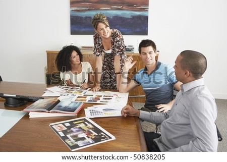 Businesspeople holding a meeting at a conference table - stock photo