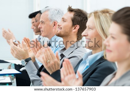 Businesspeople In A Row Greets With Clapping Hands - stock photo