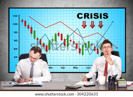 businesspeople in office and crisis chart on screen - stock photo