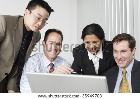 Businesspeople looking at a laptop. - stock photo