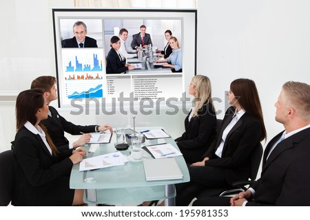 Businesspeople looking at projector screen in video conference meeting at office - stock photo