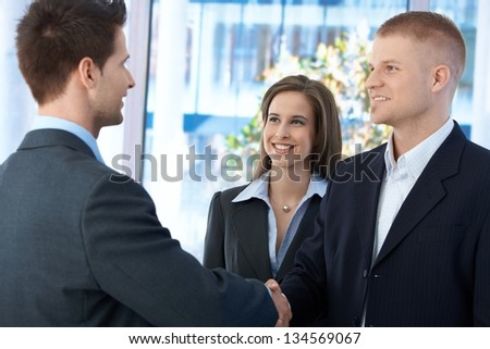 Businesspeople meeting in office, businessmen shaking hand, businesswoman smiling at introduction. - stock photo