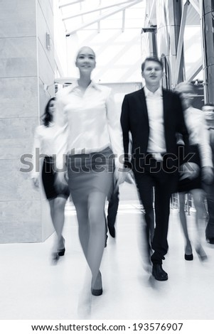 Businesspeople moving along the corridor - stock photo