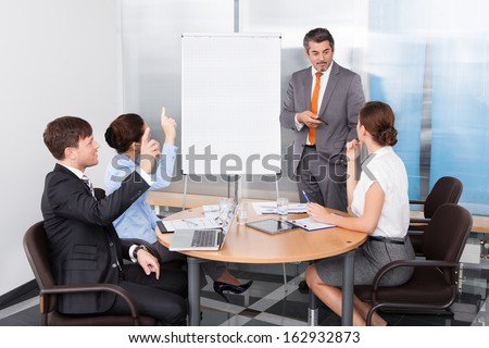 Businesspeople Raising Hands For Queries In Conference - stock photo