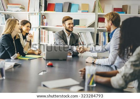 Businesspeople shaking hands in office with coworkers and staff sitting at the table with them - stock photo