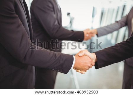 Businesspeople shaking hands with each other in the office - stock photo