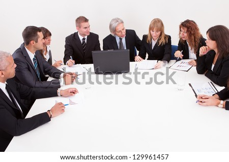 Businesspeople Sitting At Conference Table At The Meeting - stock photo