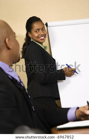 Businesspeople sitting at conference table  while businesswoman gives presentation. - stock photo