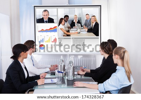 Businesspeople Sitting In A Conference Room Looking At Screen - stock photo