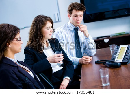 Businesspeople sitting on meeting at office listening phone during a conference call. - stock photo
