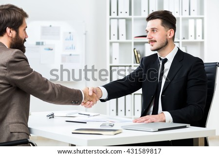 Businesspeople sitting opposite each other at office desk and shaking hands - stock photo