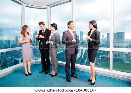 Businesspeople standing and talking in front of office window - stock photo