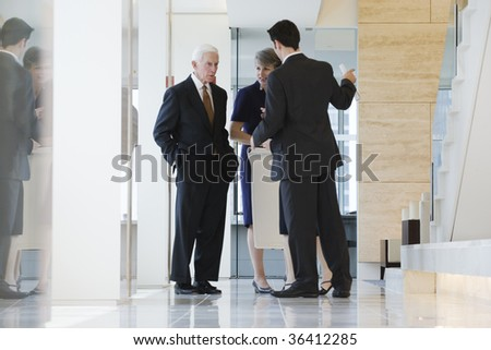 Businesspeople standing in a marbled corridor discussing plans. - stock photo