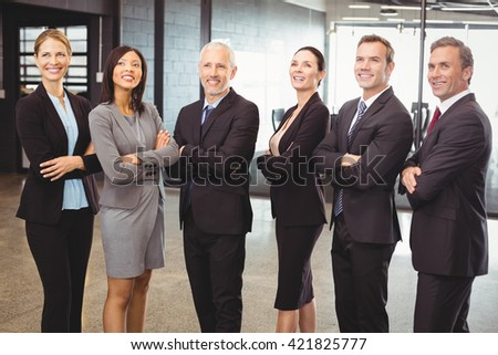 Businesspeople standing together with arms crossed in office - stock photo