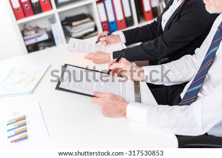 Businesspeople taking notes during training (random latin dummy text used) - stock photo