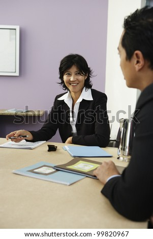 Businesspeople talking at conference table - stock photo