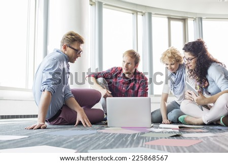 Businesspeople using laptop while sitting on floor at creative office - stock photo
