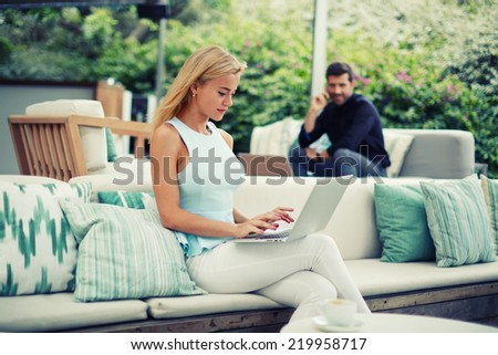 Businesspeople using technology, attractive blonde hair woman typing something on computer keyboard sitting on the terrace of modern lounge bar cafe,success businessman having cell mobile conversation - stock photo