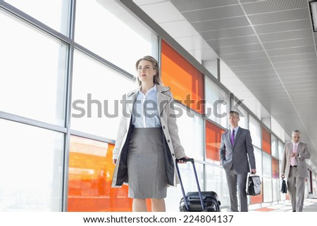 Businesspeople walking on train platform - stock photo