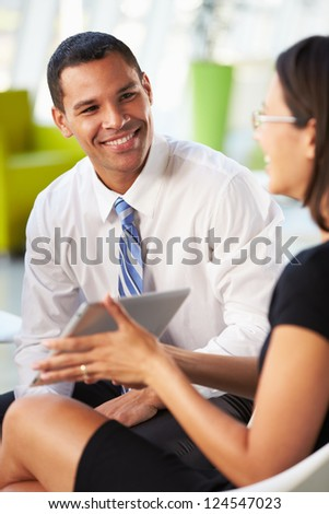 Businesspeople With Digital Tablet Having Meeting InOffice - stock photo