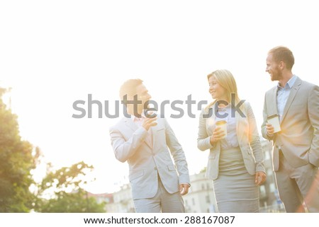 Businesspeople with disposable cups conversing against clear sky on sunny day - stock photo