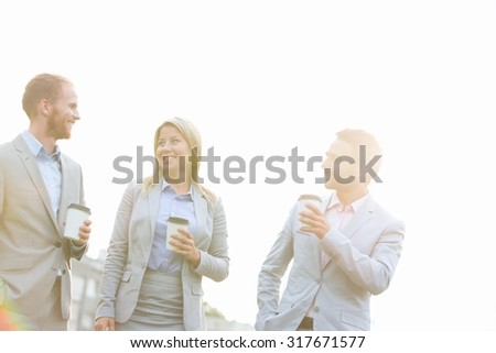 Businesspeople with disposable cups talking against clear sky on sunny day - stock photo