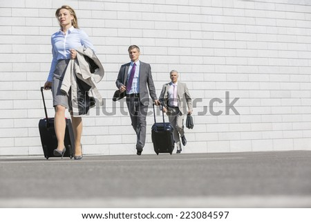 Businesspeople with luggage walking on street - stock photo