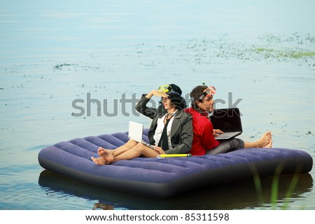 Businesspeople with notebook sitting on inflatable mattress and looking at different way - stock photo