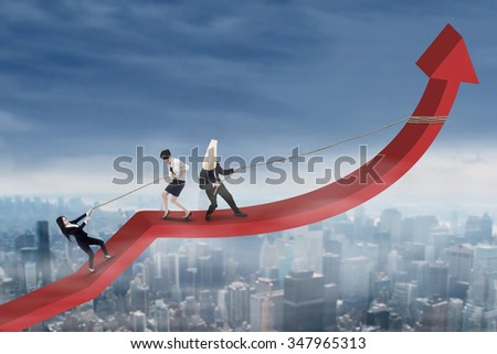 Businesspeople work together to climb and pulls financial graph above the city - stock photo