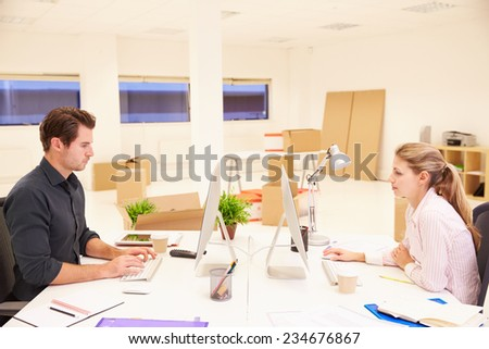 Businesspeople Working At Desks In New Office - stock photo
