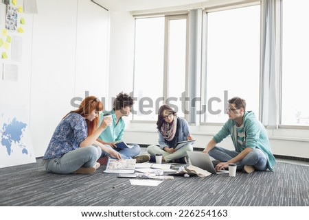 Businesspeople working on floor at creative work space - stock photo