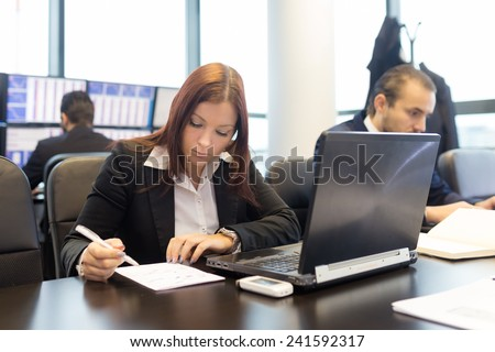 Businesspeople working on laptops in modern office. - stock photo