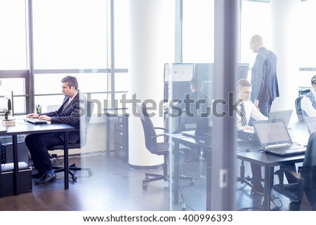 Businesspeople working on laptops in modern office. Business, entrepreneurship and team work concept. - stock photo