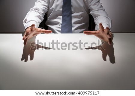 Businessperson at empty office desk about to grab something. Mock up - stock photo